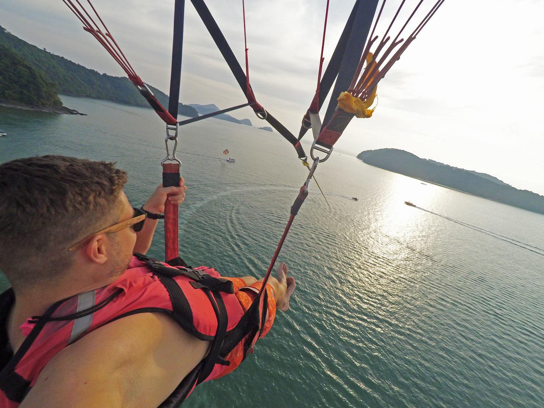 Parasailing, an einem Fallschirm hinter einem Motorboot hergezogen werden