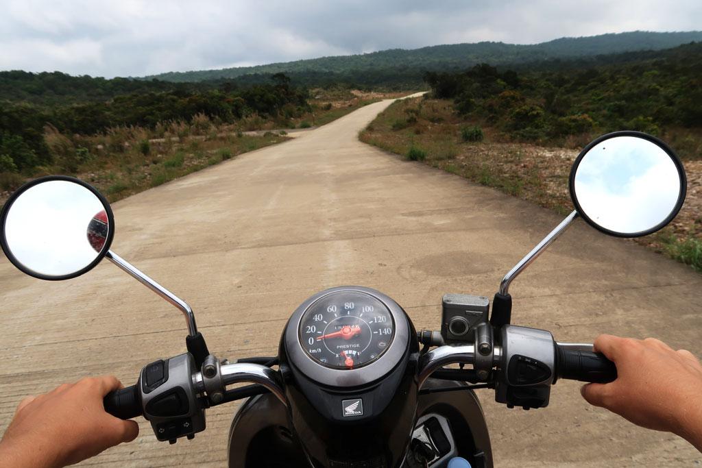 Die Sicht vom Roller auf die Straße im Bokor Nationalpark in Kampot