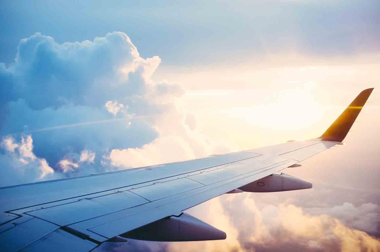 Die Perspektive von einem Platz im Flugzeug hoch oben in den Wolken bei strahlendem Sonnenschein