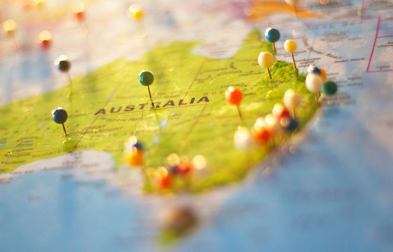 Auf einer australischen Landkarte stecken viele bunte Pinnadeln