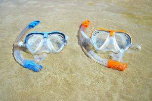 Zwei bunte Taucherbrillen liegen am Strand im Wasser