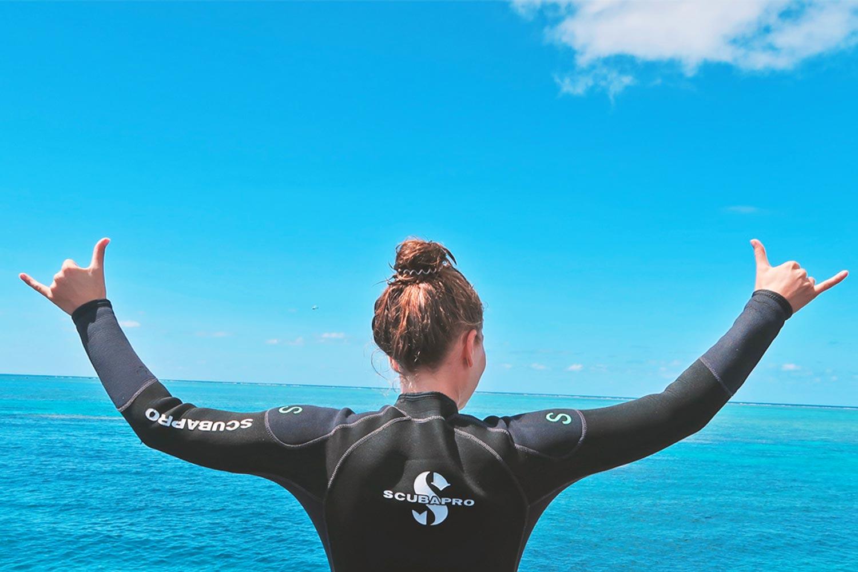 Linda steht glücklich mit erhobenen Händen auf einem Katamaran im Great Barrier Reef