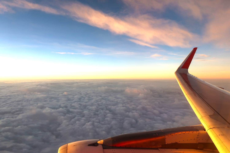 Wie findet man günstige Flüge - Unsere Top-Tipps! - Aussicht über den Wolken im Flugzeug