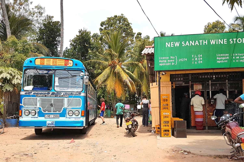 Srilankesischer Bus an einer Haltestelle vor einem Sprituosengeschäft