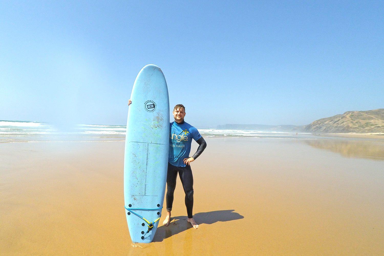 Kevin mit einem Surfbrett an der Algarve